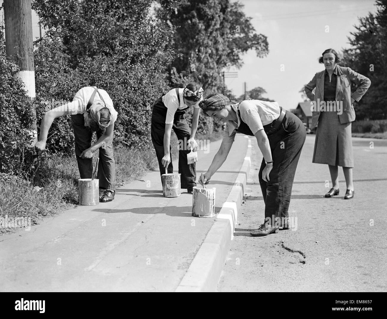 Las mujeres camino pintores, 1941. Las mujeres que realizan trabajos de hombres pintar el bordillo blanco, por lo Imagen De Stock