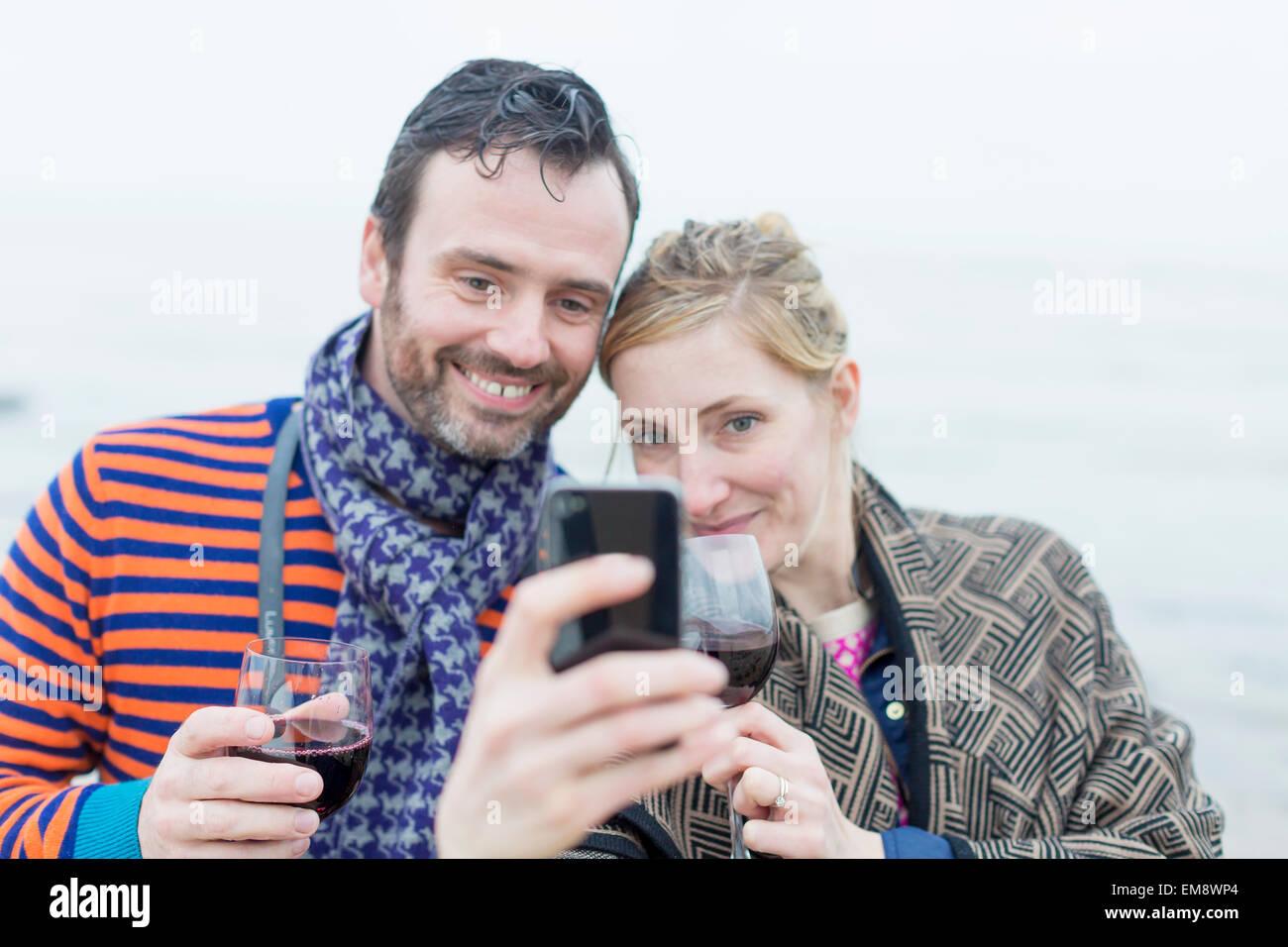 Pareja en la playa, bebiendo vino, teniendo autorretrato con el smartphone Foto de stock