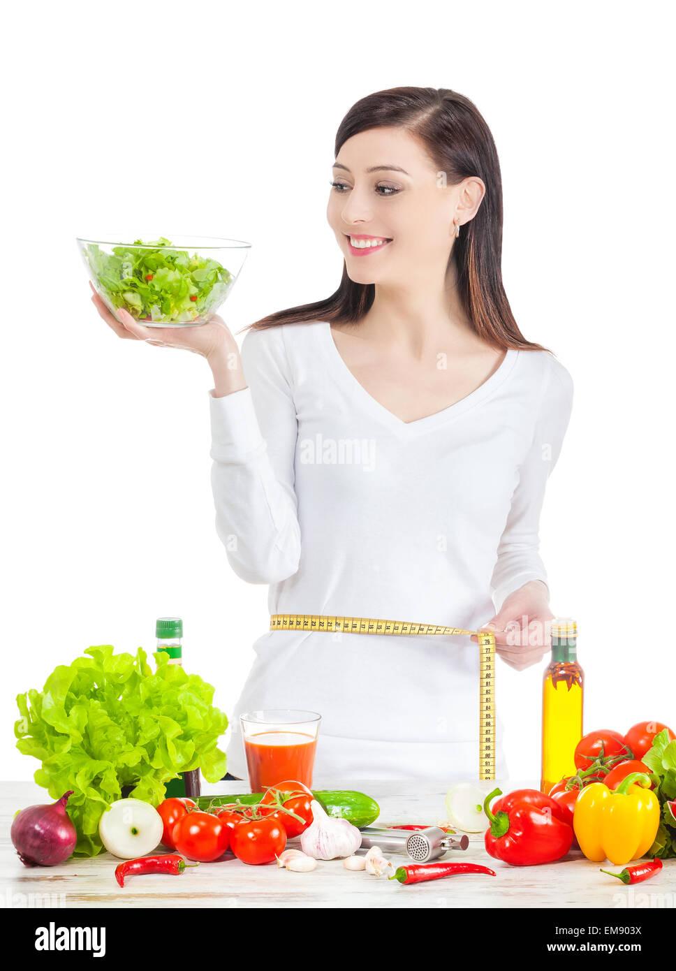 Joven Mujer feliz con ensalada, midiendo su cintura. Comida sana ans concepto de estilo de vida. Foto de stock