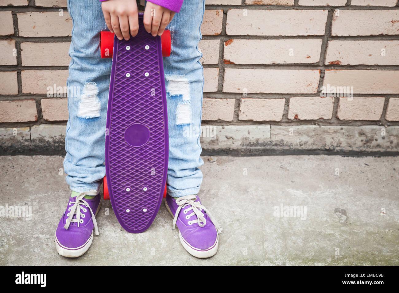 Adolescente en jeans y gumshoes posee cerca de monopatín urbano gris pared de ladrillo Imagen De Stock