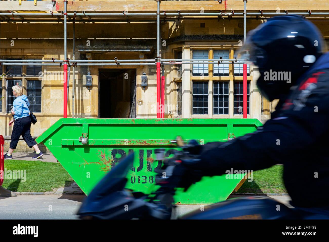 Basura saltar fuera de casa en Chipping Campden, siendo renovado, Gloucestershire, Inglaterra Imagen De Stock