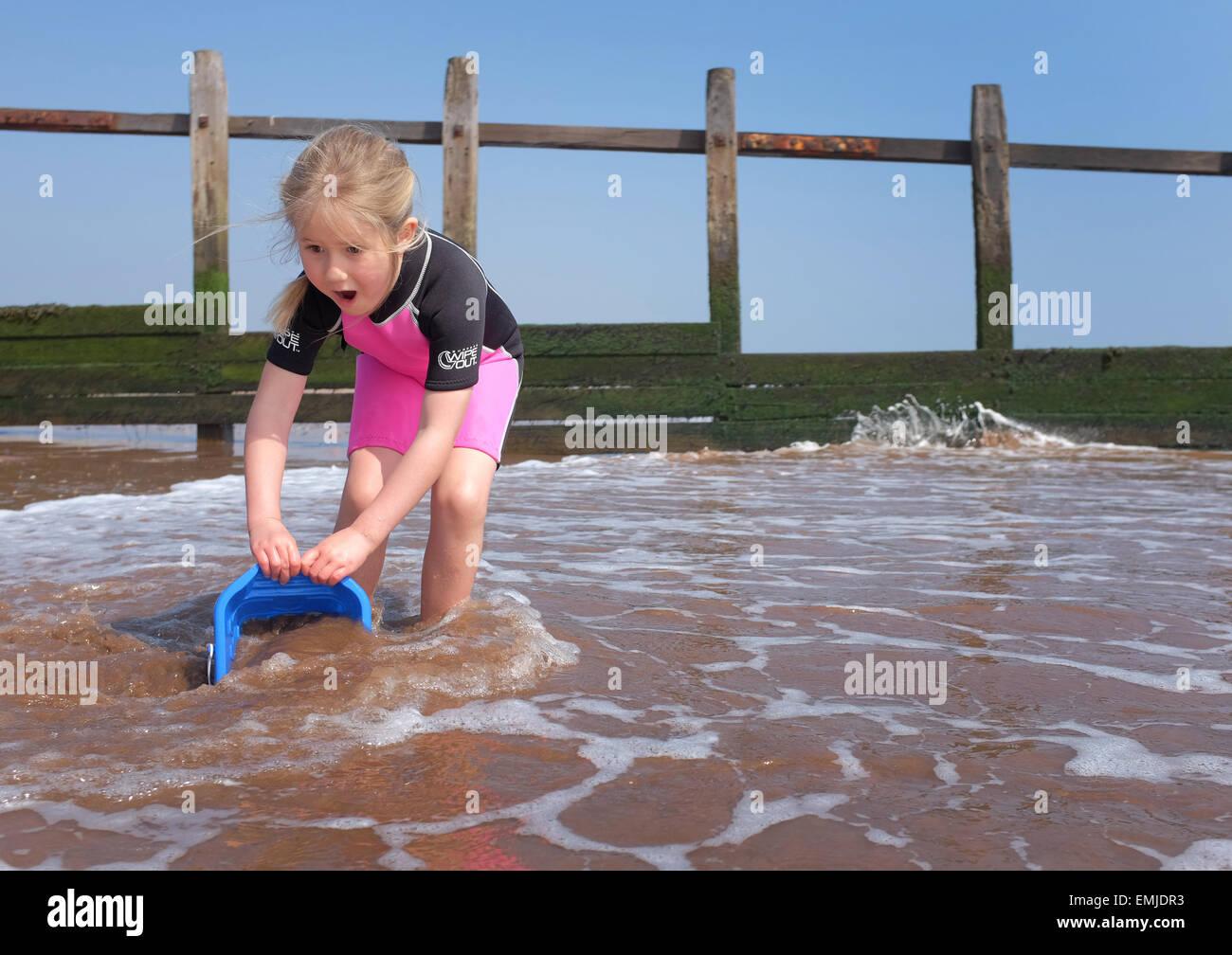 Una joven en un traje de neopreno para recoger el agua con una cuchara en la playa UK Imagen De Stock