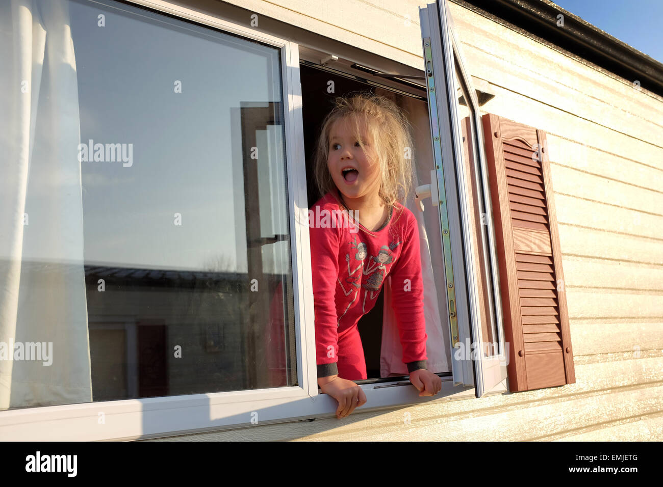 Una joven en su pijama mira por la ventana de una caravana, en el inicio de un nuevo día Imagen De Stock