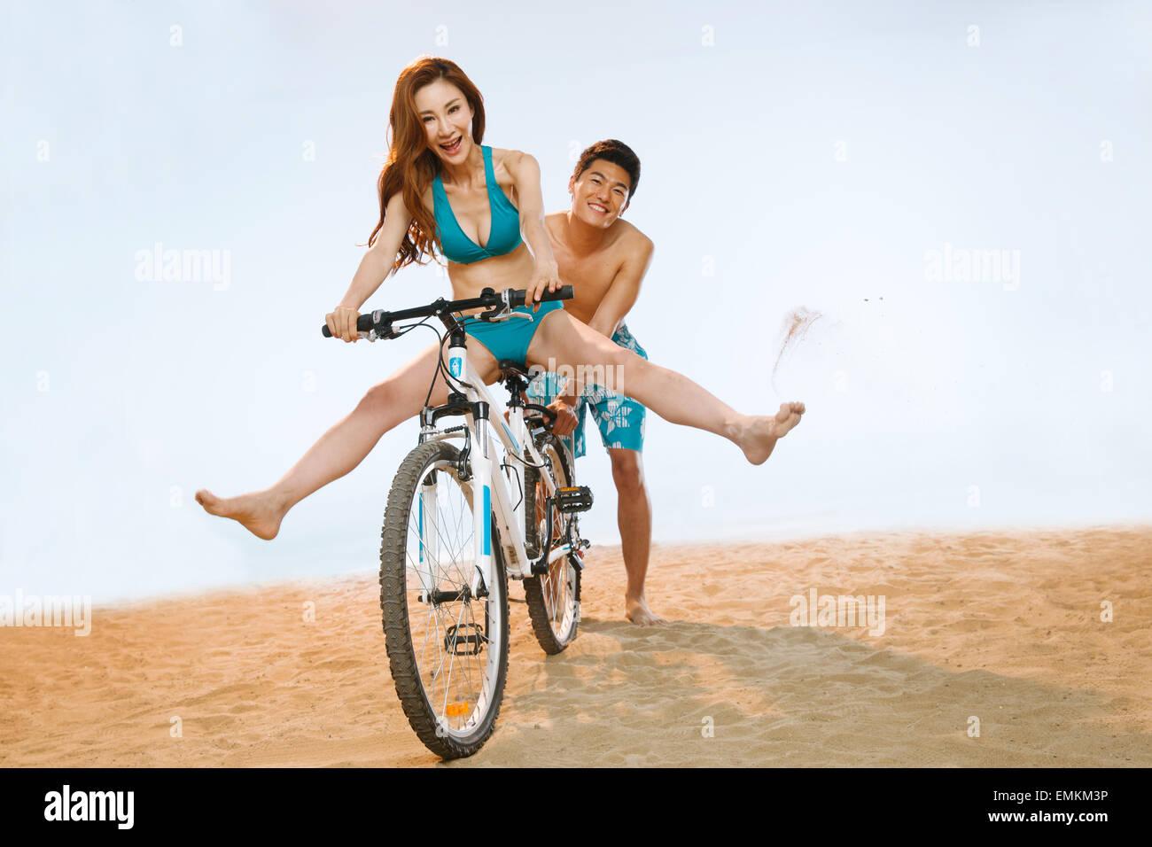 Pareja romántica a montar una bicicleta en la playa Foto de stock