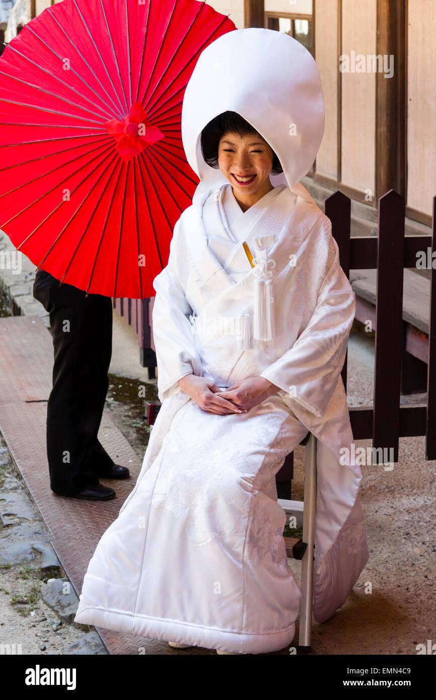 Japón, Nara, Tamukeyama santuario. Novia sentada en el tradicional japonés shiromuku kimono blanco, sonriendo con sombrilla roja, paraguas de papel detrás de ella. Foto de stock