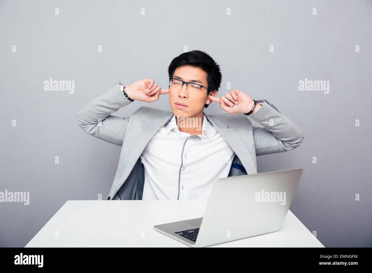 Guapo empresario asiático sentado en la mesa y cubriendo sus orejas sobre fondo gris Imagen De Stock