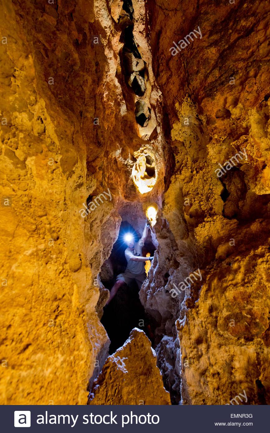 Guías turísticos casco luz atravesando la oscuridad navega bajo la perla formación Colossal Cave, Imagen De Stock