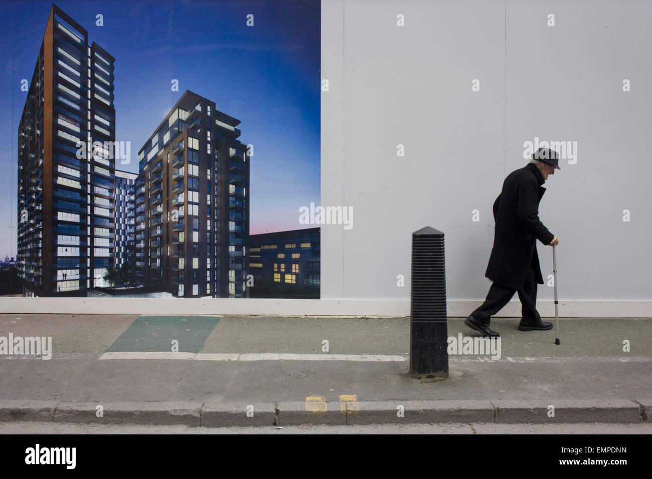 Anciano camina doblada pasado un proyecto de regeneración en el acaparamiento de imagen en Elephant & Castle, Imagen De Stock