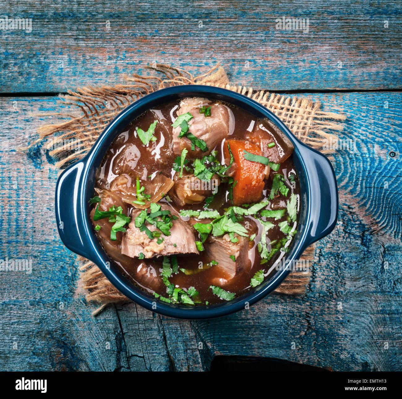 Guiso de carne con verduras y hierbas en mesa de madera antigua Imagen De Stock
