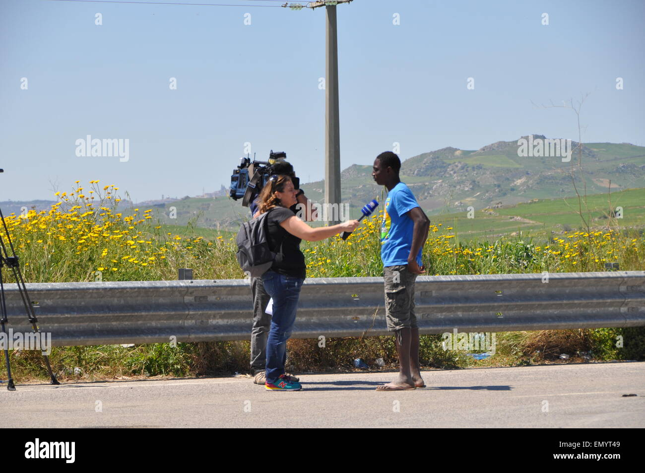 Los periodistas entrevistaron a un migrante en frente del centro de detención de Mineo, en Sicilia, Italia, Martes, 22 de abril de 2015. Aunque los migrantes pueden ir y venir como lo deseen, sin los documentos adecuados, es inútil tratar de escapar. Según el Director del Centro, actualmente hay más de 3.200 migrantes, en su mayoría subsaharianos que están gastando años aquí esperando el asilo político. También hay más de 200 grupos étnicos en el centro. (CTK Foto/Tereza Supova) Foto de stock
