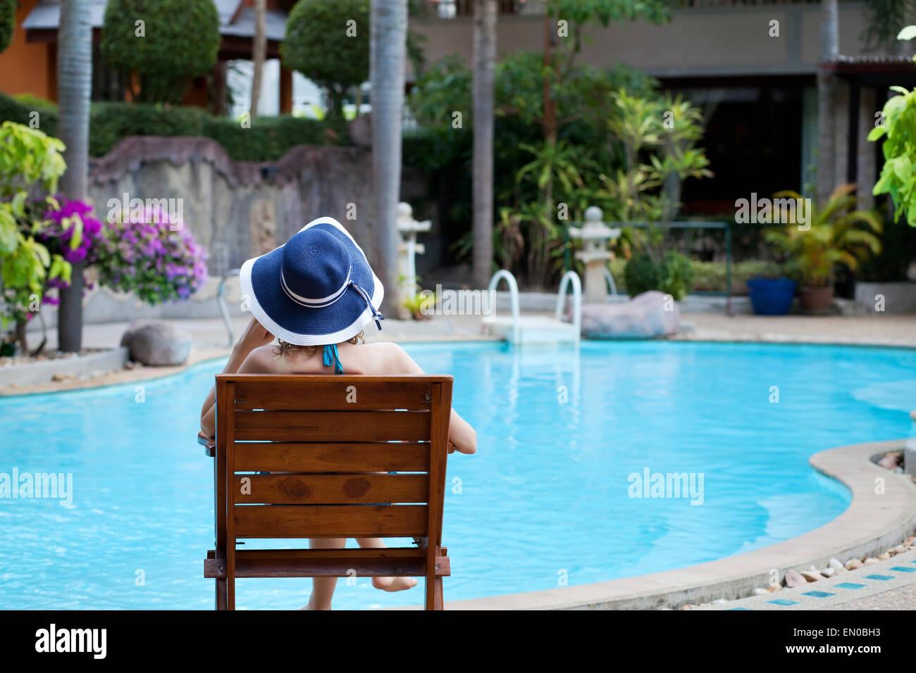 Mujer relajante en el spa del hotel de lujo cerca de la preciosa piscina Foto de stock
