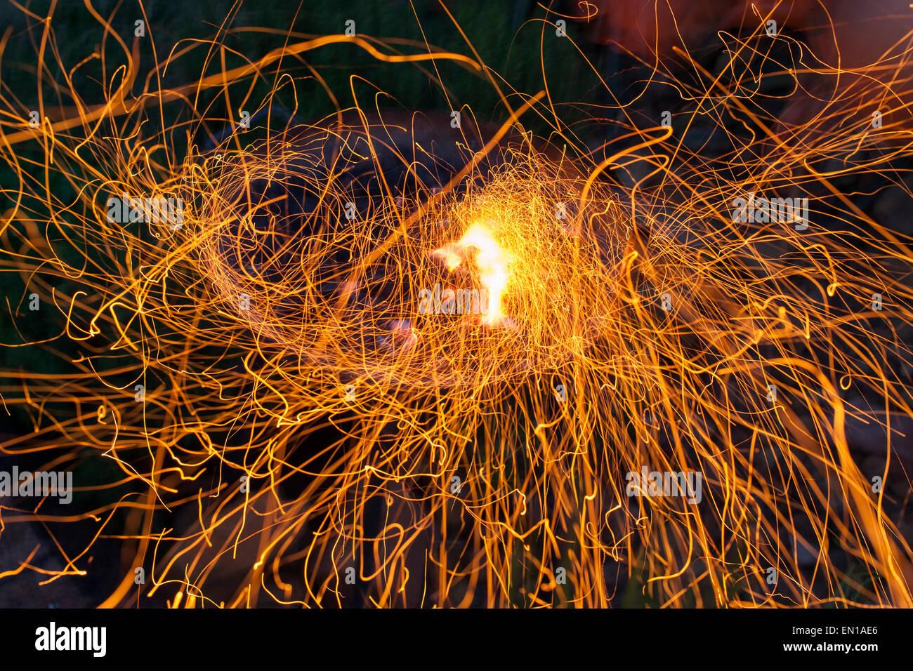 La larga exposición de chispas volando de un asado al fuego. Imagen De Stock