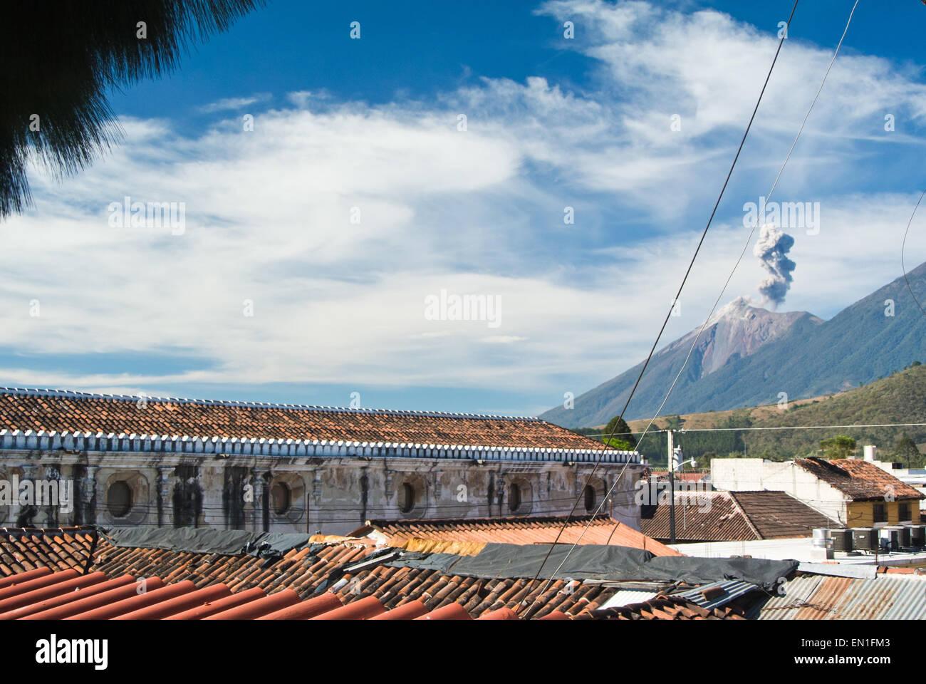 Volcán de fuego activo, visto a través de los tejados de la Antigua, Guatemala Imagen De Stock