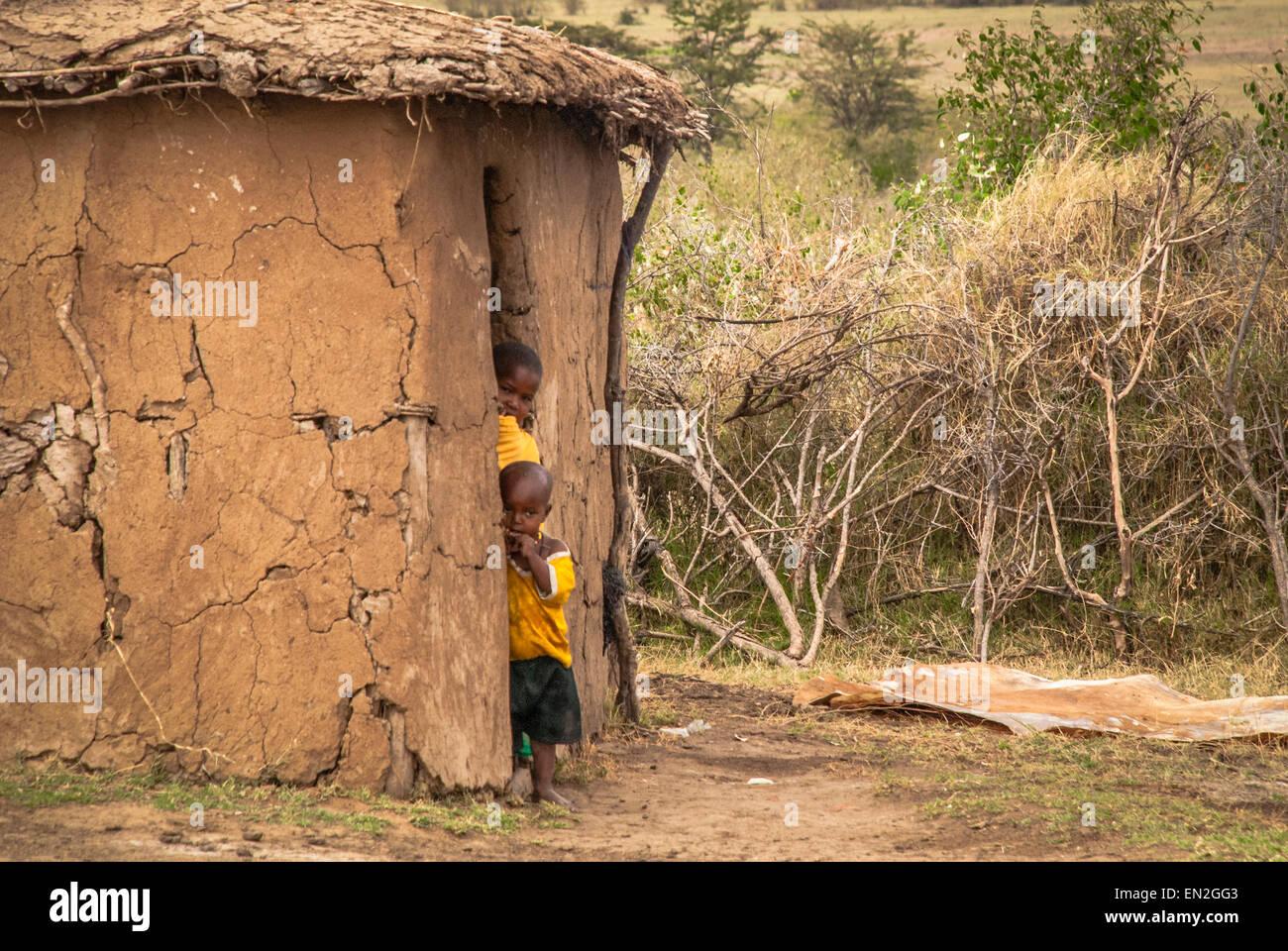 Dos pequeños niños masai asomarán desde una choza de barro en una aldea Masai. Las chozas forman Imagen De Stock