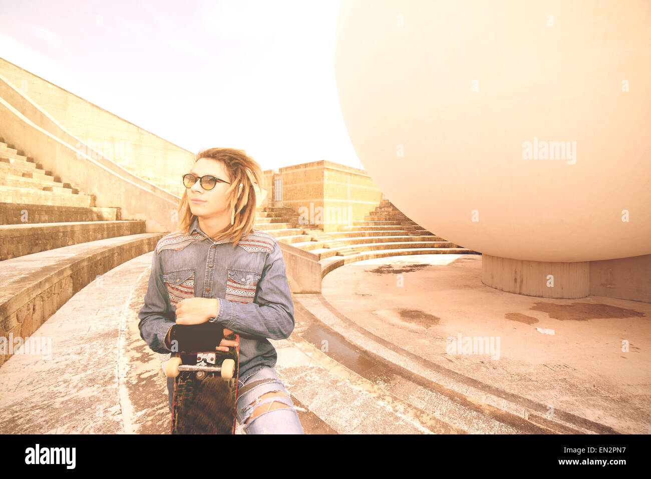 Retrato de joven con pelo rasta y skate en un concepto de estilo de vida Imagen De Stock