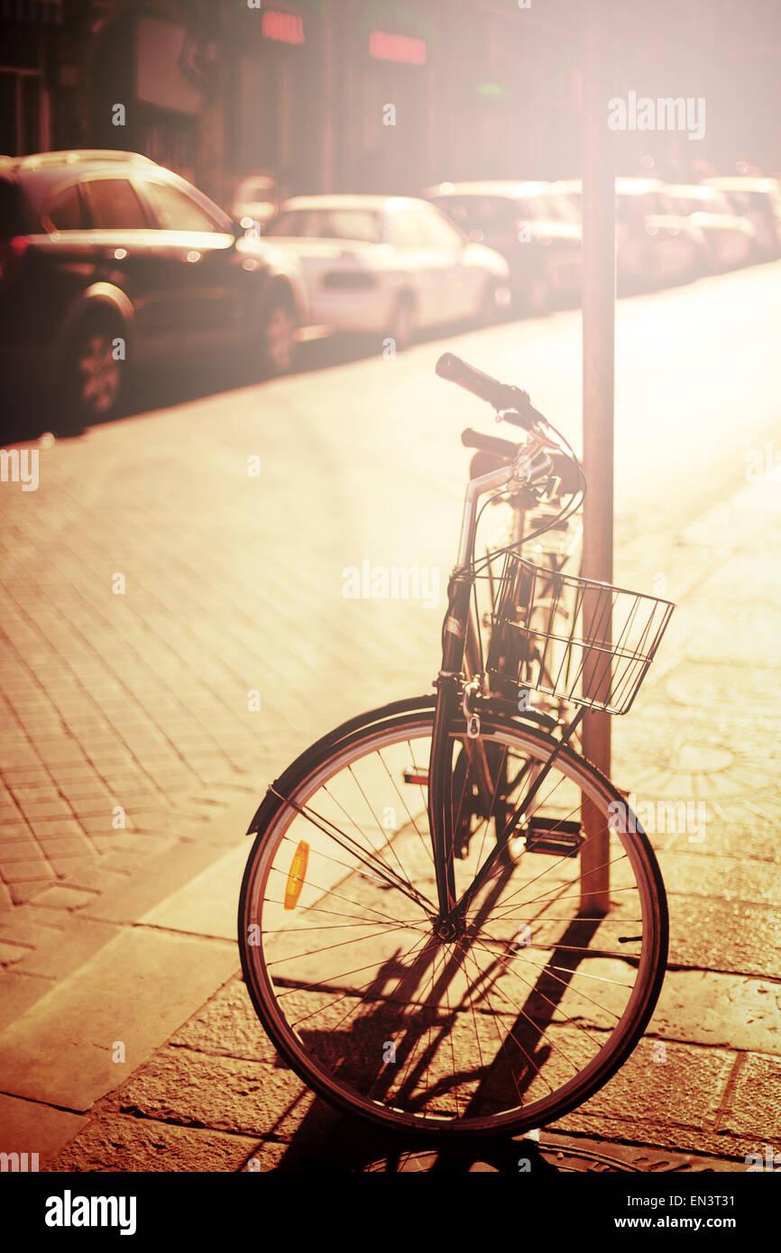Bicycle descansando en la calle. Efecto Instagram, la imagen en tonos de colores clásicos. El enfoque selectivo. Imagen De Stock