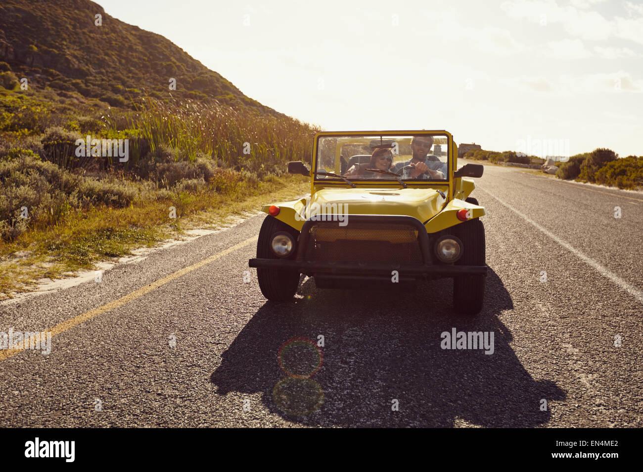 Pareja joven conduciendo un coche en una carretera abierta. Pareja joven en viaje por carretera en verano. Imagen De Stock