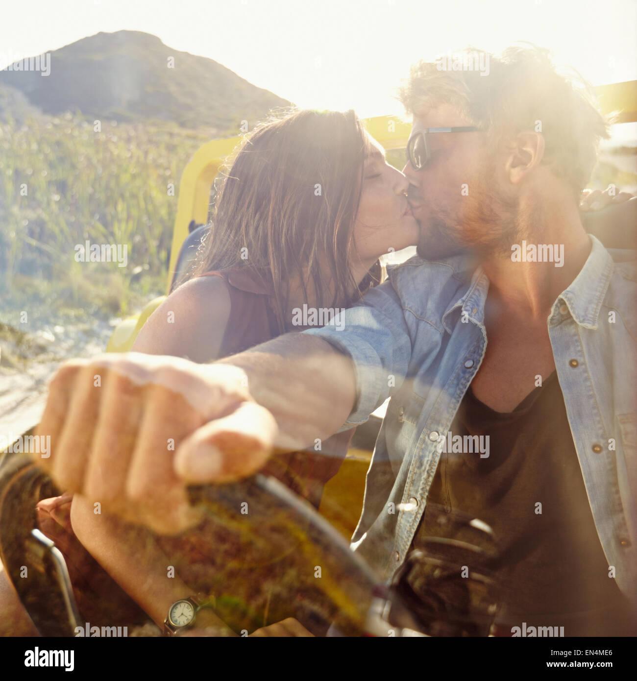Joven pareja besándose en el coche. Pareja en amor en Road Trip a divertirse. Imagen De Stock