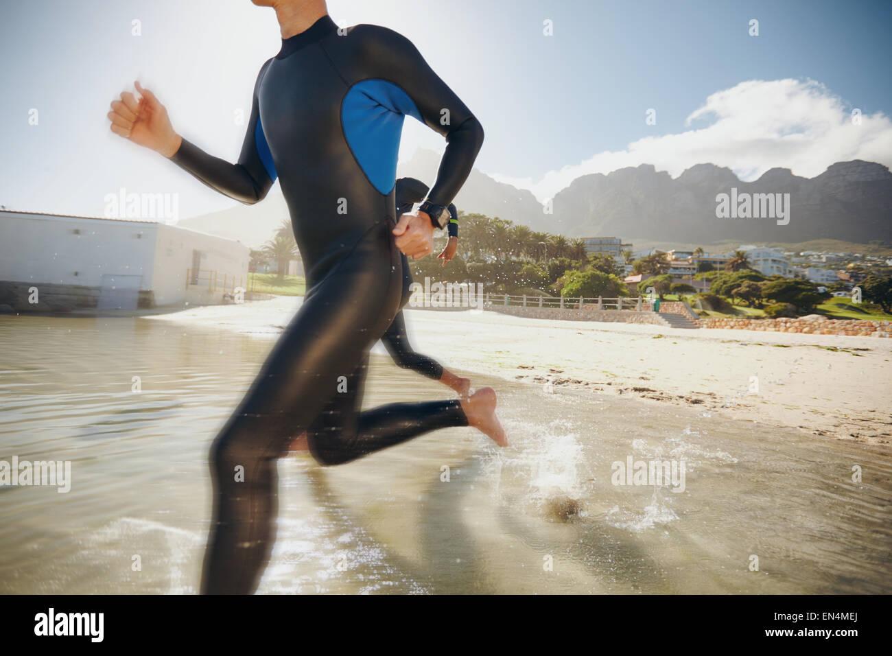 Imagen de dos triatletas corriendo en el agua. Atleta corriendo en el agua, entrenamiento para un triatlón. Foto de stock