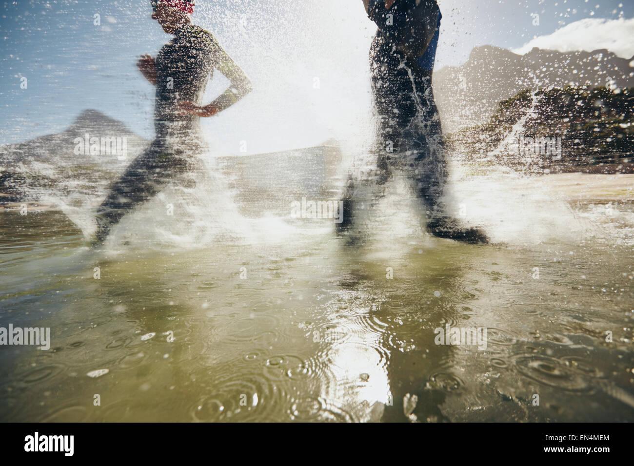 Imagen de las salpicaduras de agua mientras triatletas corriendo en el lago. Los atletas entrenamiento para triatlón Imagen De Stock
