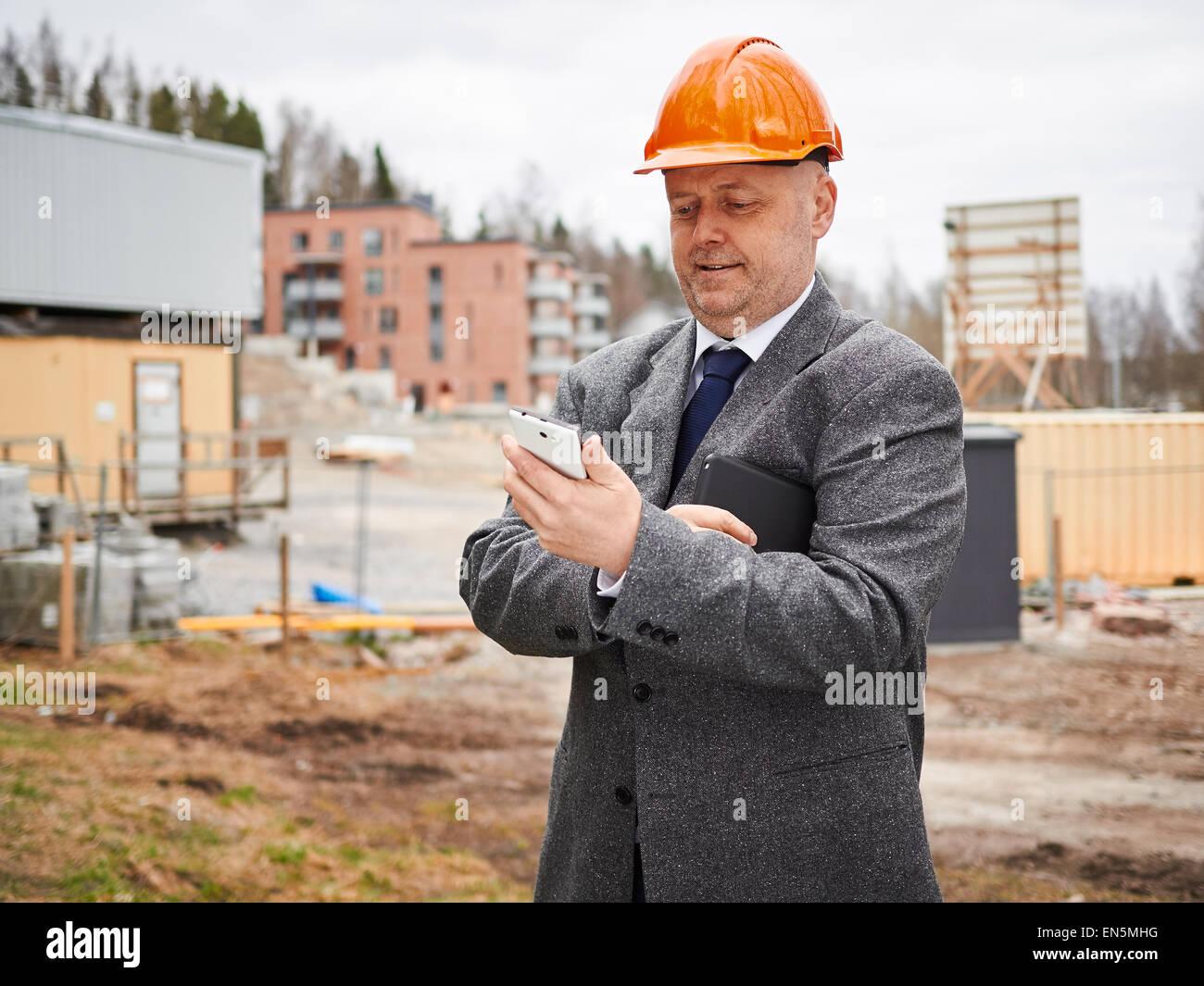 Ingeniero macho utiliza teléfono celular, él vistiendo el traje y el sombrero duro, construcción Imagen De Stock