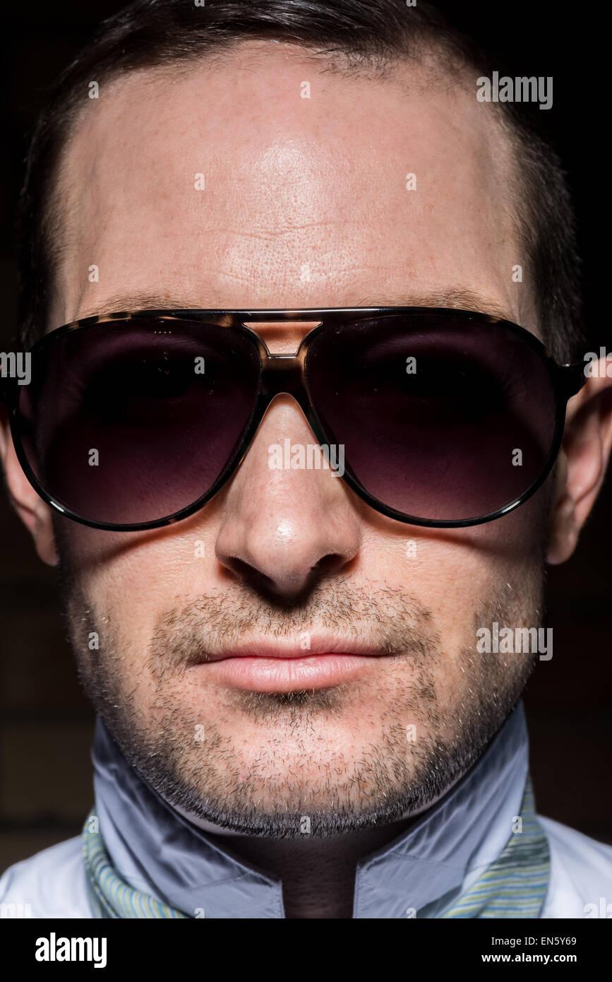 f5b1872eee Apretado retrato de un hombre que confía con iluminación de alto contraste  con gafas de sol. Con barba rastrojo.
