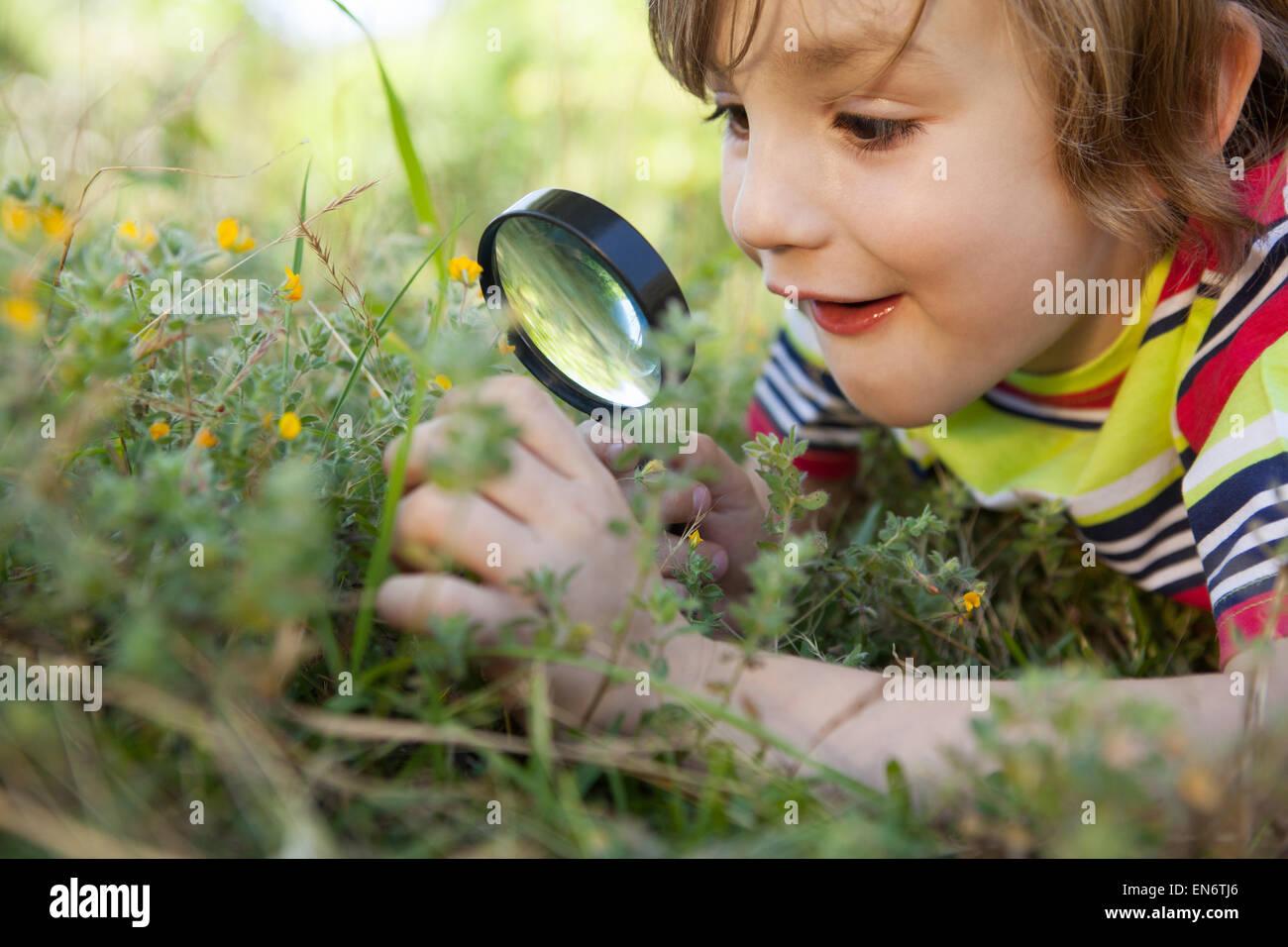 Poco feliz Chico mirando a través de una lupa Imagen De Stock