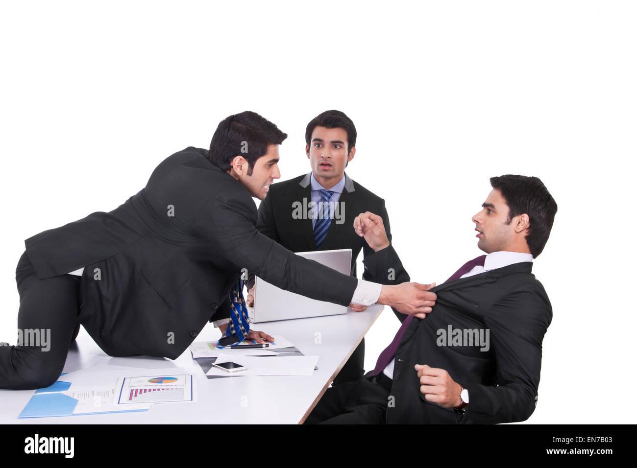 Empresario obteniendo violento con compañeros de negocios Imagen De Stock