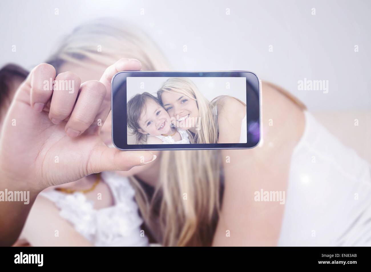 Imagen compuesta de mano sujetando el smartphone mostrar Imagen De Stock
