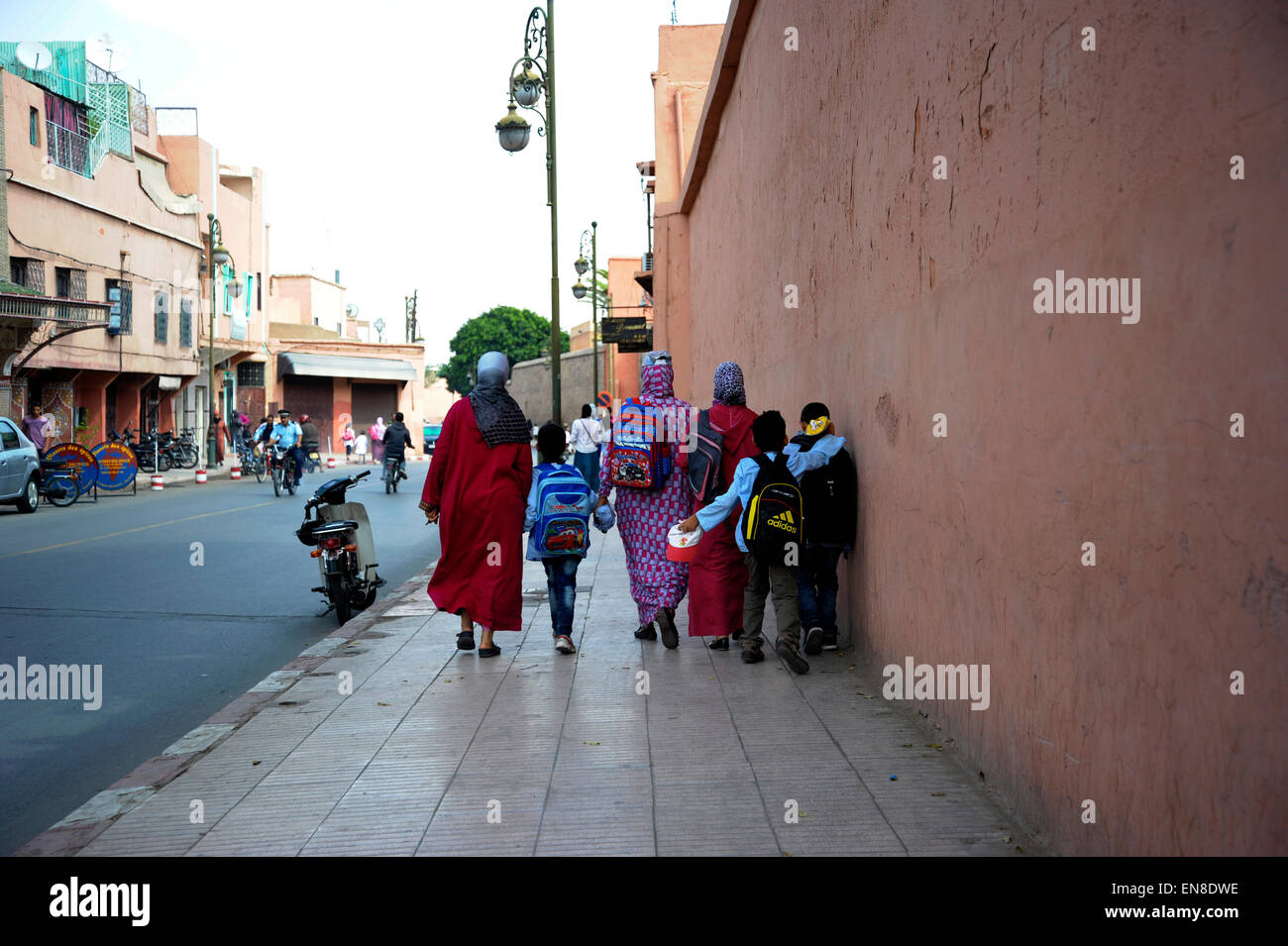 Familia regresando de la escuela en la escuela a lo largo de una carretera principal en el norte de África Imagen De Stock