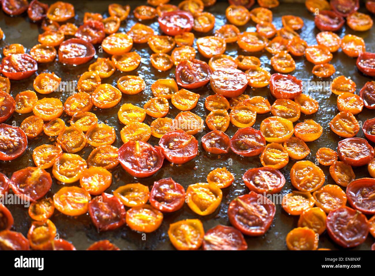Amarillo y rojo asado tomates cherry en una hoja bandeja. Imagen De Stock