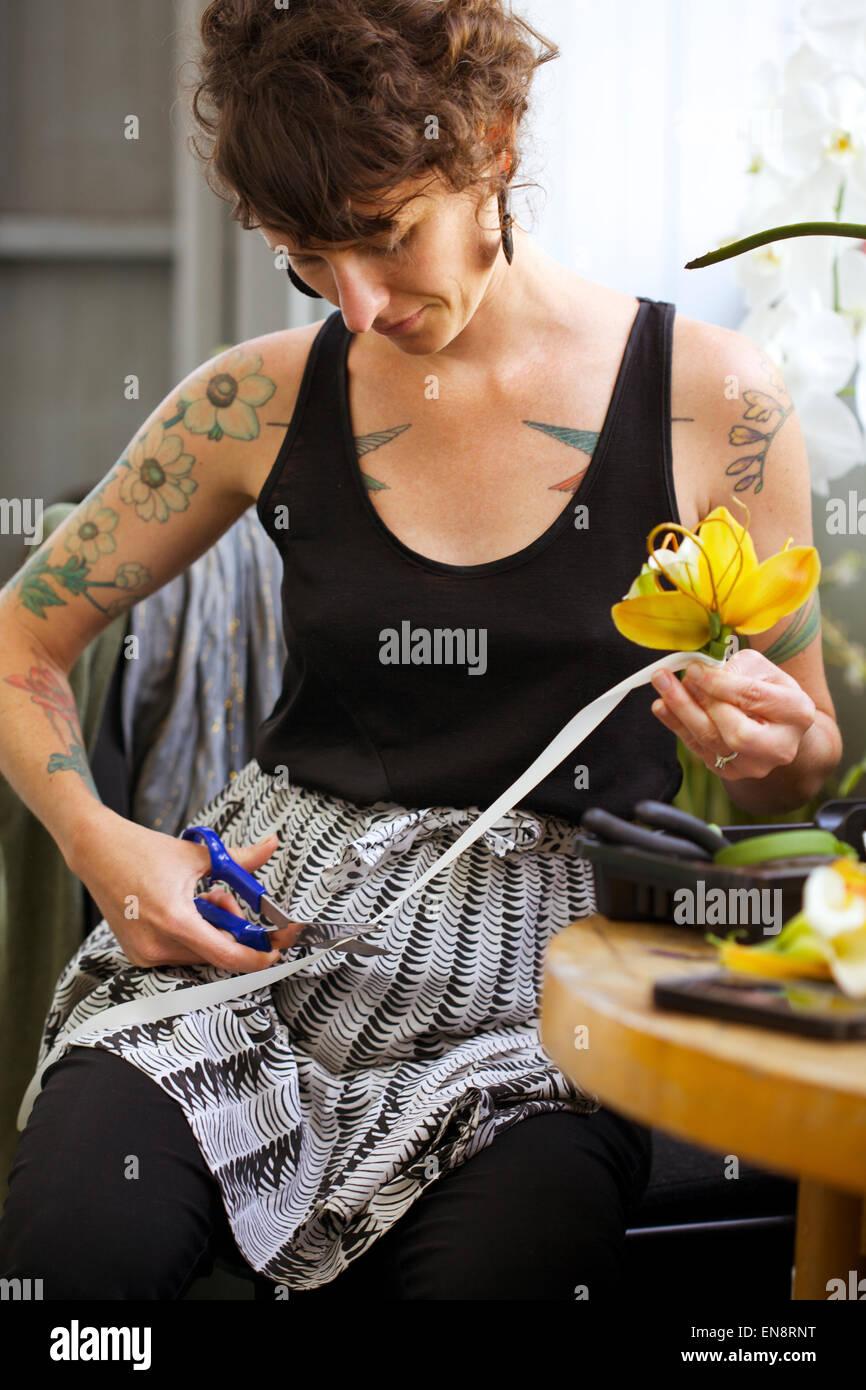 Una mujer tatuada floristería corta la cinta blanca en un arreglo floral para la solapa del novio de una orquídea Imagen De Stock