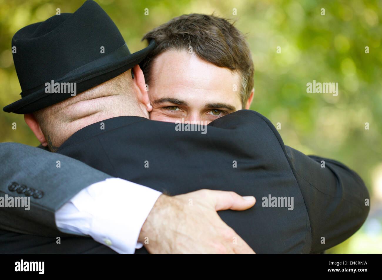 Dos hombres abrazando, la una en frente de la cámara hace contacto visual con el espectador. Imagen De Stock