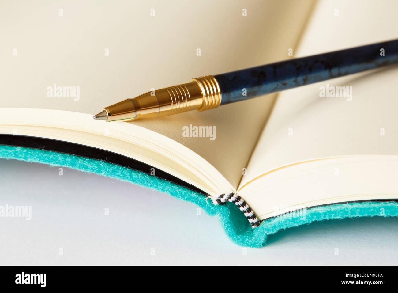 Abrir bloc de notas en blanco con un bolígrafo en la página sobre una superficie plana, de fondo blanco. Imagen De Stock