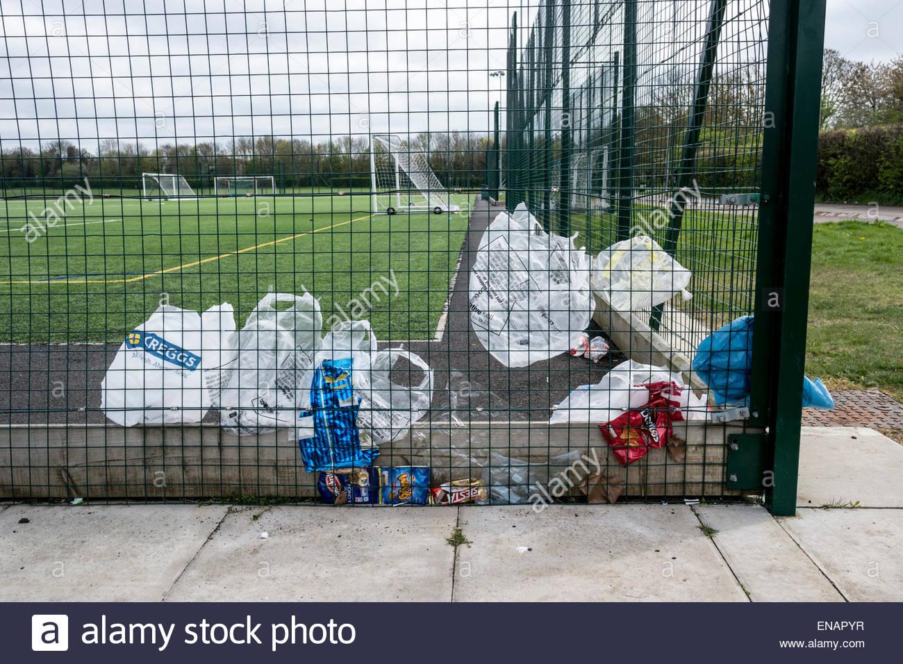Las bolsas de plástico atrapada en una valla en un campo de deportes para todo clima exterior Imagen De Stock