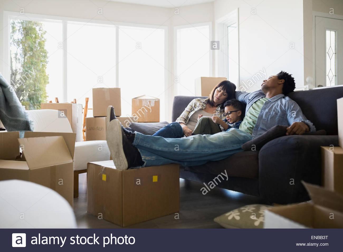 Cajas de mudanza en torno de la familia en el sofá relajante Foto de stock