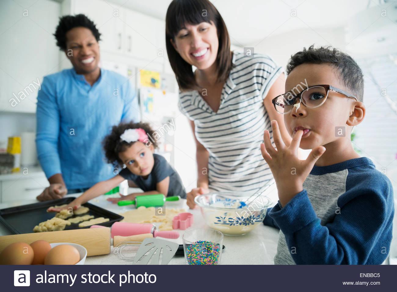 Chico con masa de galleta lamiendo el dedo en la nariz Imagen De Stock
