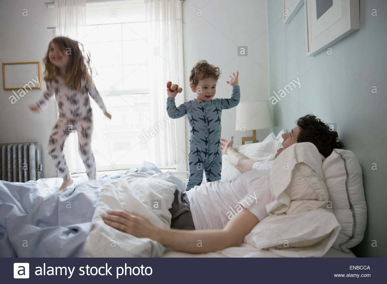 El padre y los hijos en pijama jugando en la cama Imagen De Stock