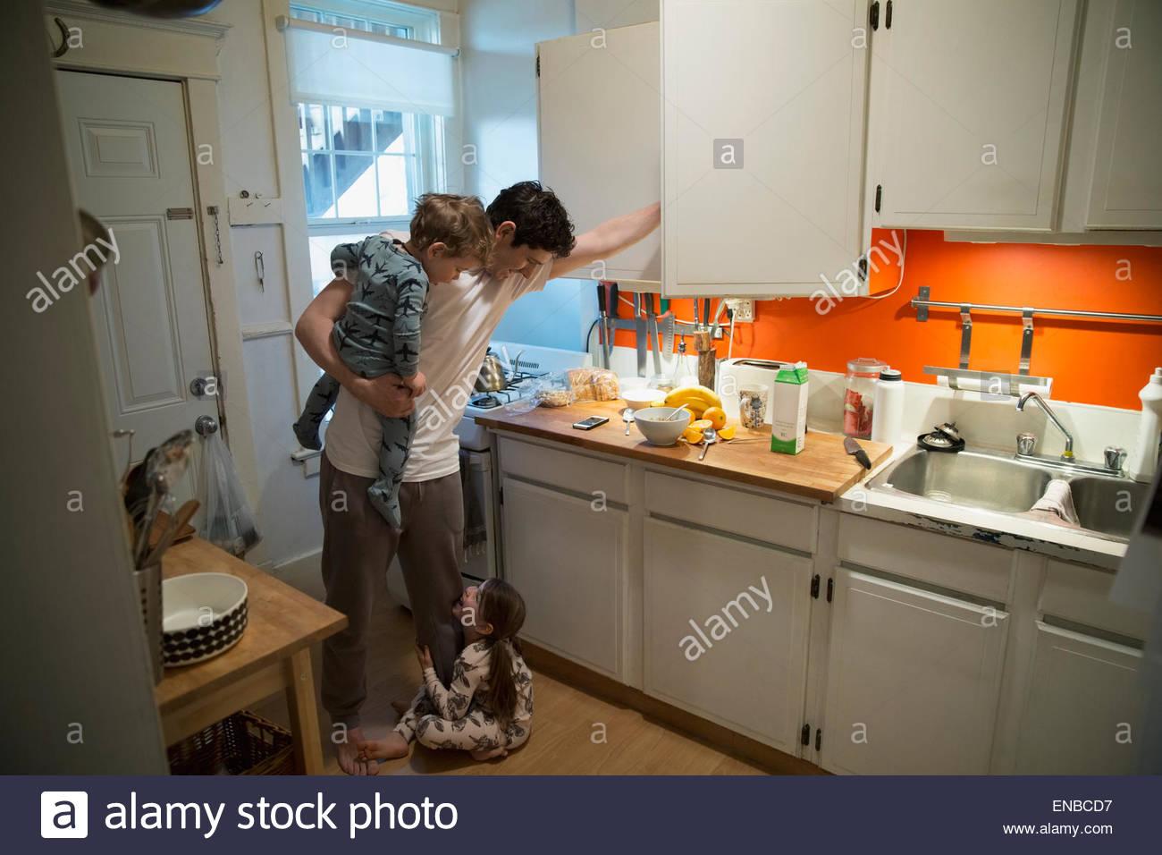 El padre y los hijos en pijama en la cocina Imagen De Stock