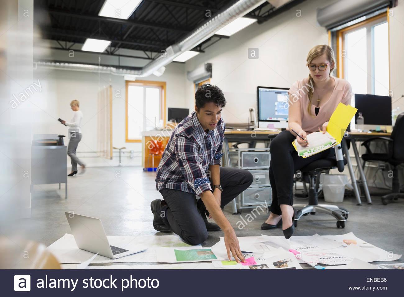 Diseñadores gráficos reunión revisando las pruebas sobre el suelo de su oficina Imagen De Stock