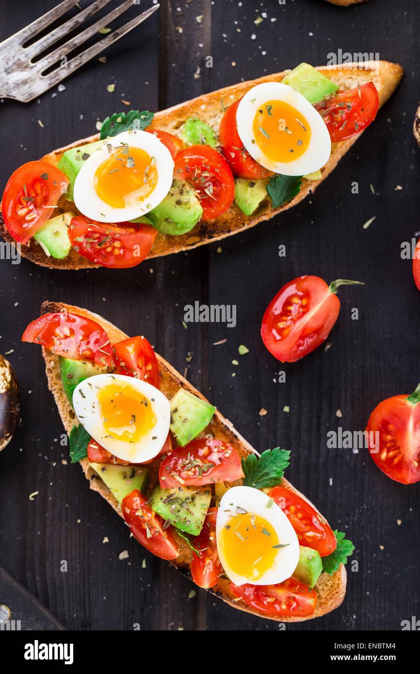 Bruschetta con tomate, aguacate y huevo de codorniz sobre una tabla de madera Foto de stock