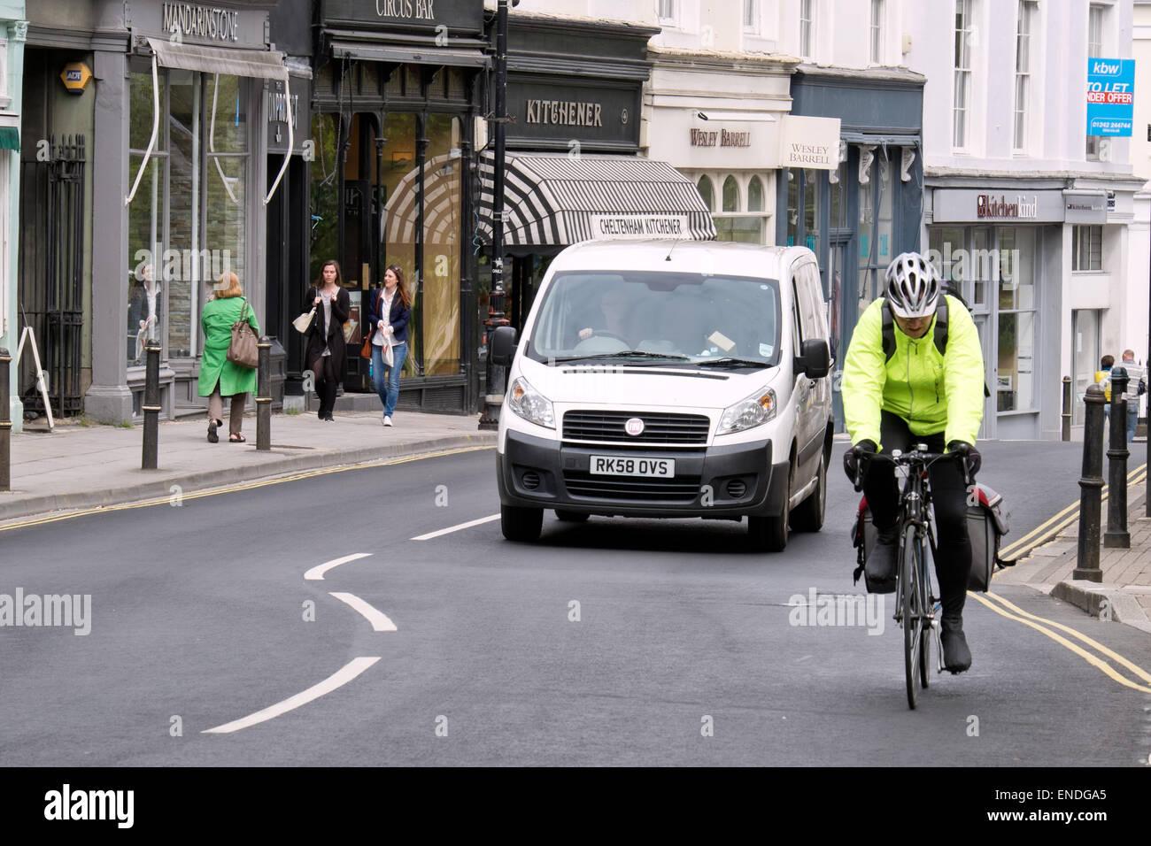 Un van superando un ciclista vistiendo ropa de seguridad en una calle de compras en Montpellier, Cheltenham, UK Imagen De Stock