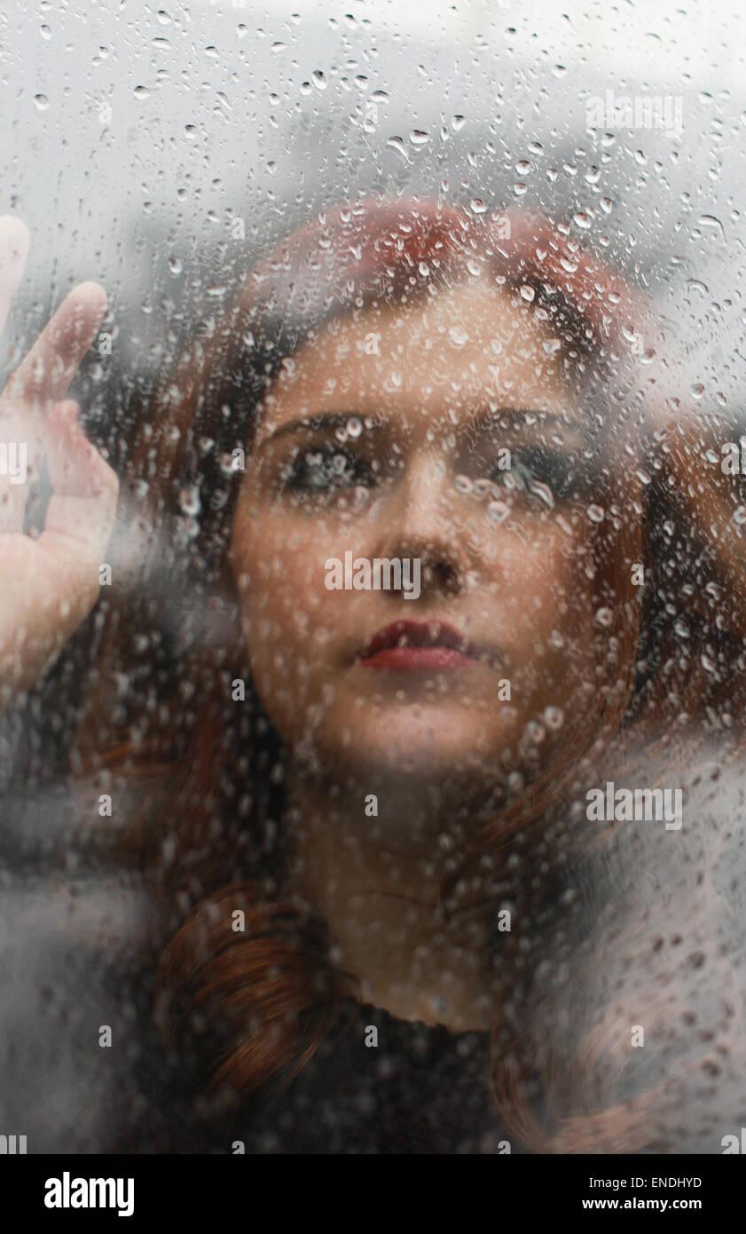 Pretty girl mirando por una ventana que está cubierto en las gotas de lluvia Imagen De Stock
