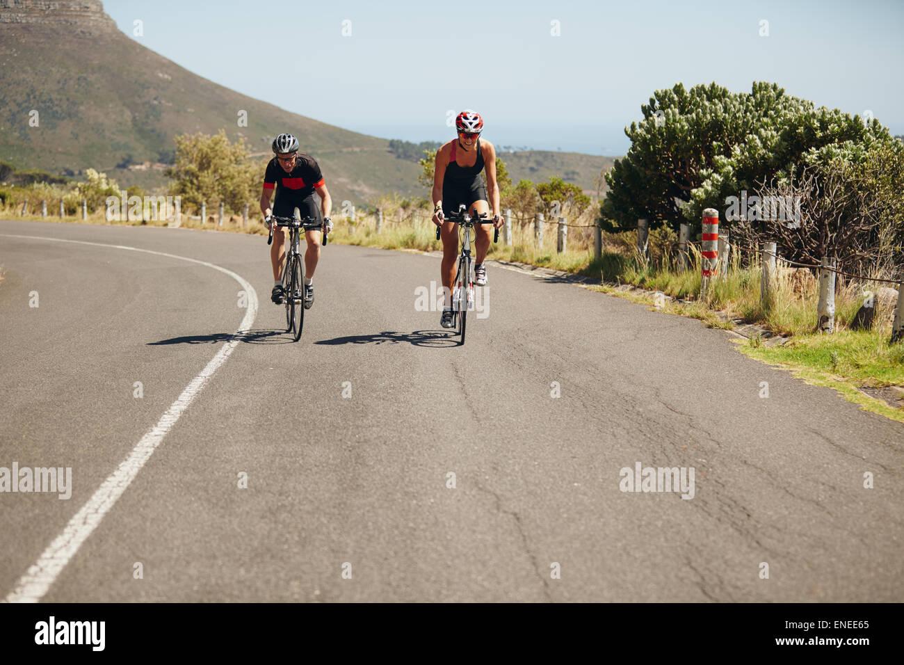 Ciclista bicicletas en carretera abierta. Triatletas ciclismo en bicicletas. Practicando para triatlón de la Imagen De Stock