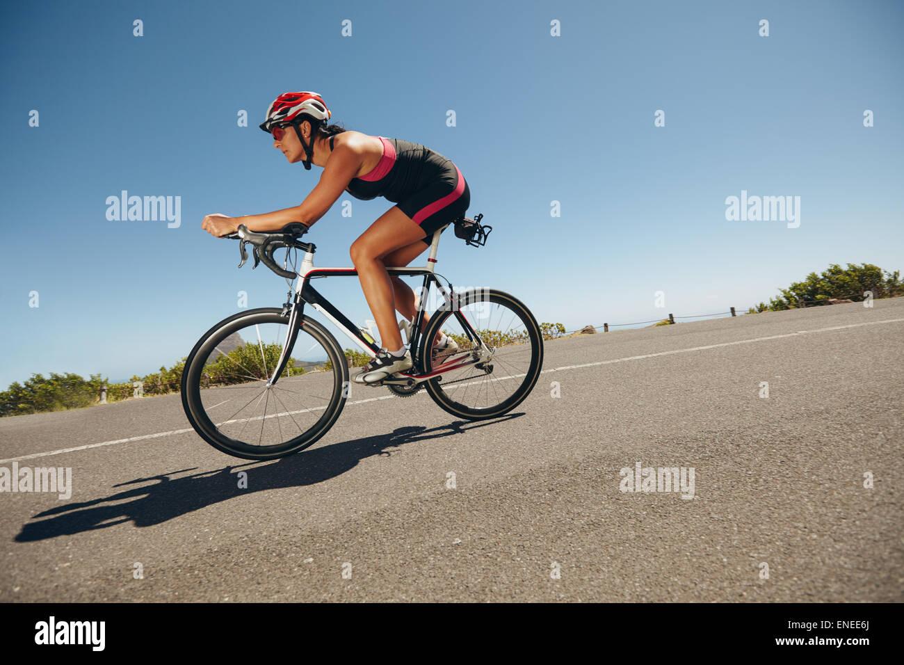 Ciclista femenina en un país por carretera entrenamiento para la competencia. Mujer joven montando bicicleta Imagen De Stock