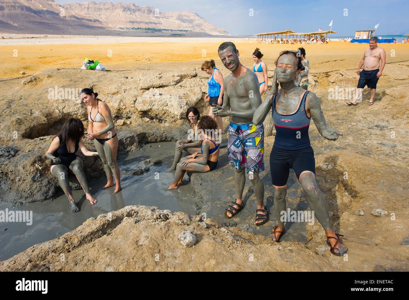 El Mar Muerto, ISRAEL - Oct 13, 2014: la gente rozan con el barro en la playa del Mar Muerto en Israel Imagen De Stock