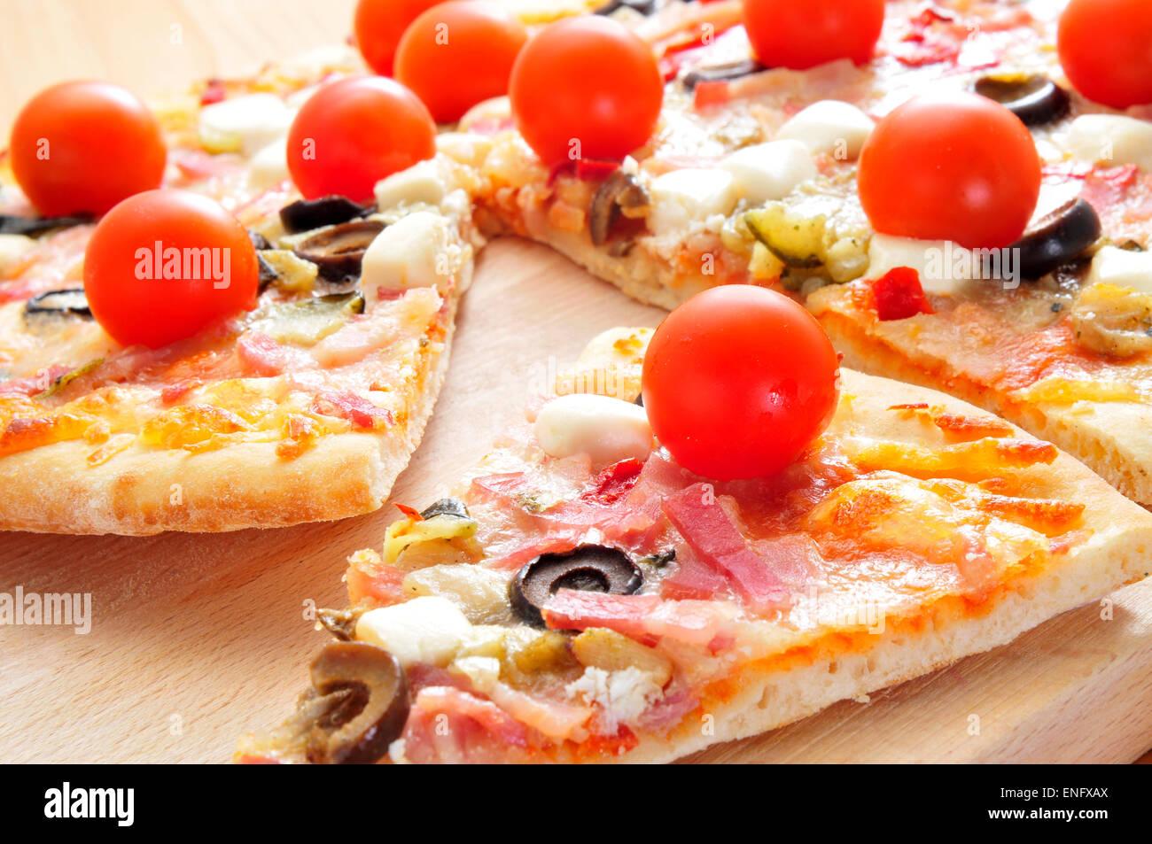 Algunas rebanadas de pizza con bacon, aceitunas, tomates cherry, queso de cabra, pimiento verde y berenjena Foto de stock