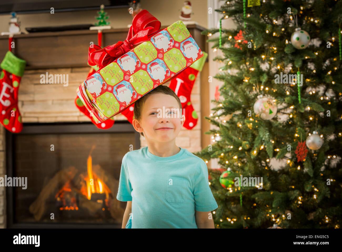 Muchacho caucásico equilibrando su regalo de Navidad en la cabeza. Foto de stock