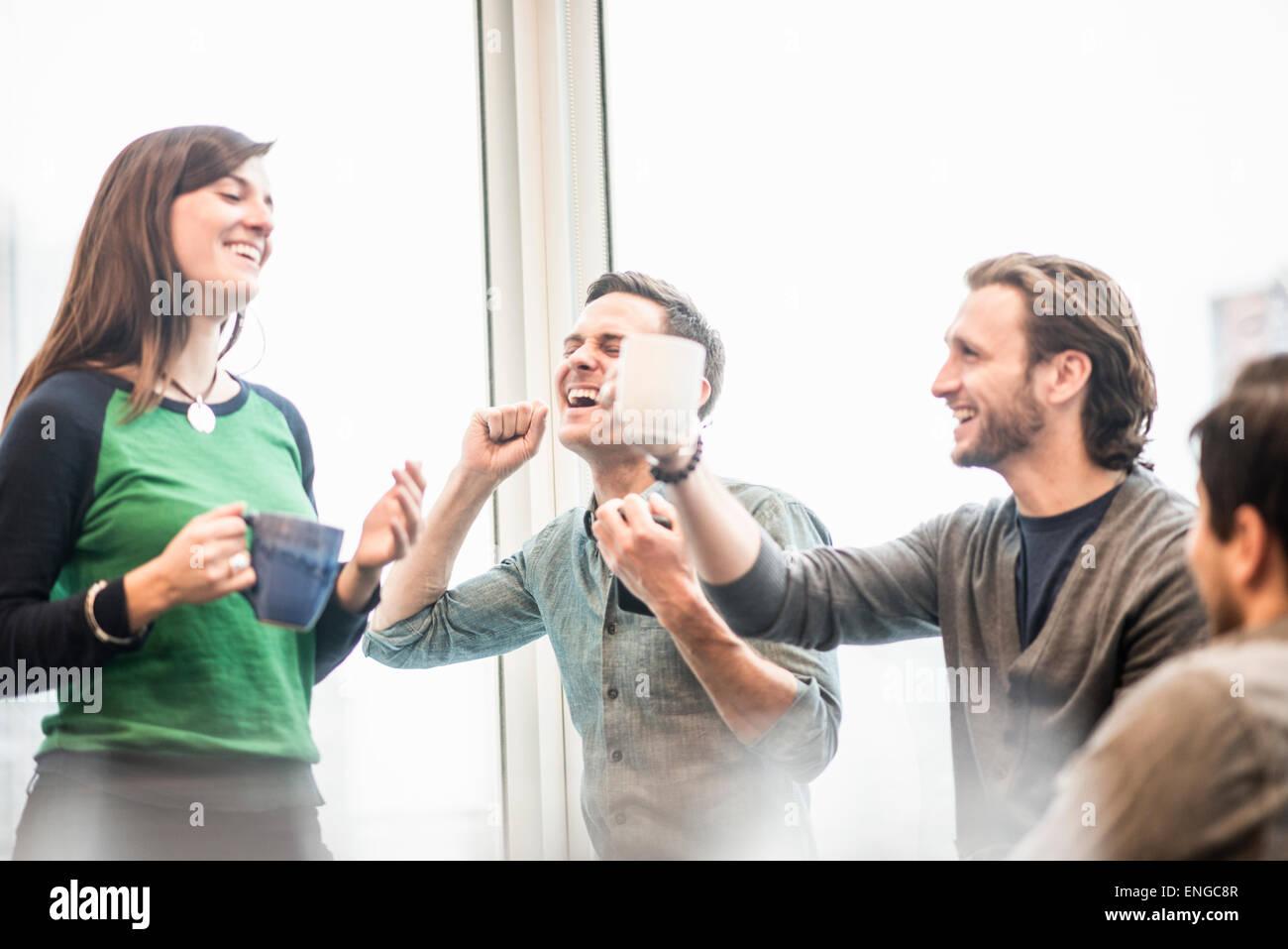 Cuatro compañeros de trabajo en un descanso, riendo y elevando sus tazas de café. Imagen De Stock
