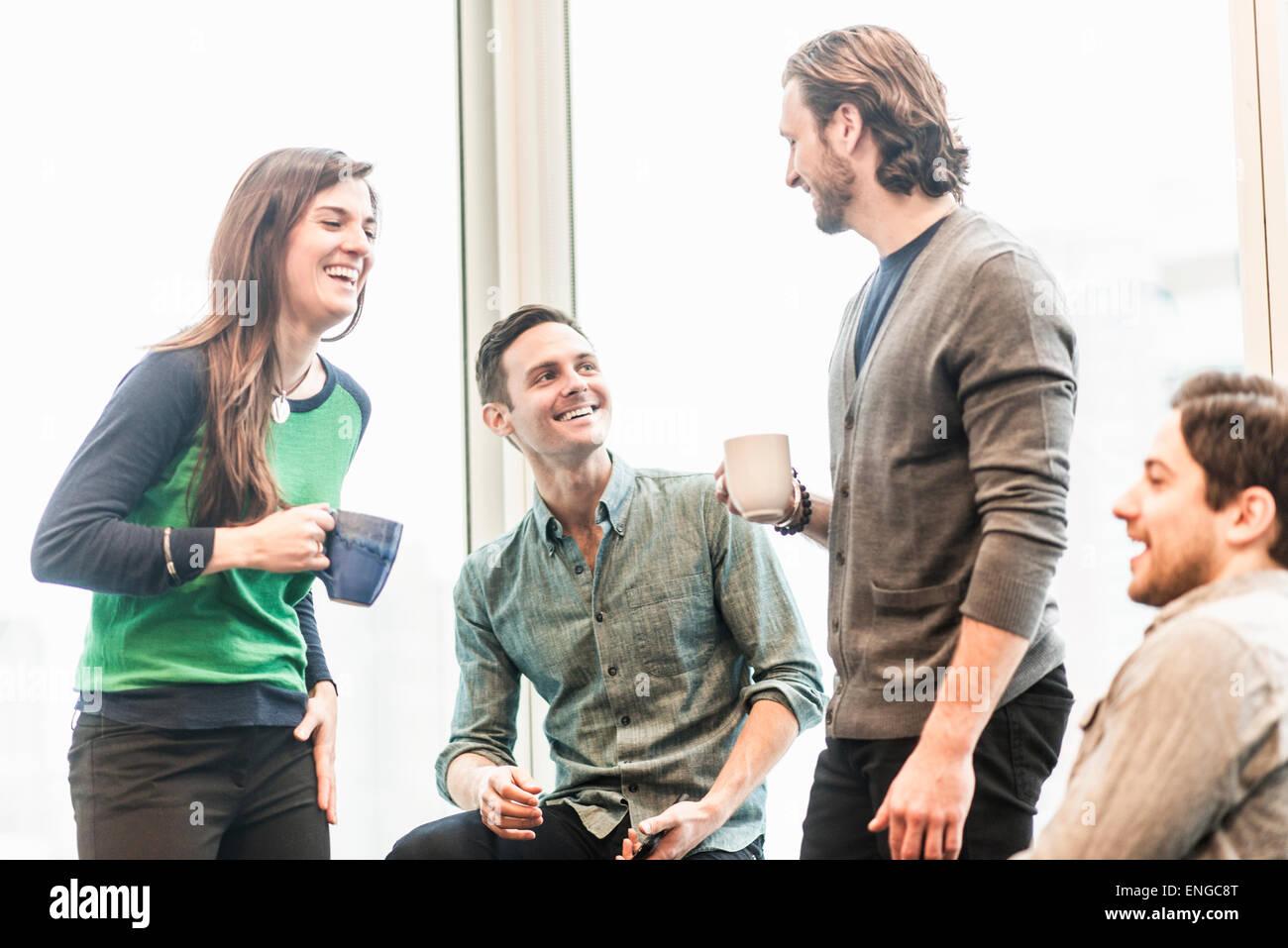 Cuatro compañeros de trabajo en un descanso, riendo juntos. Imagen De Stock